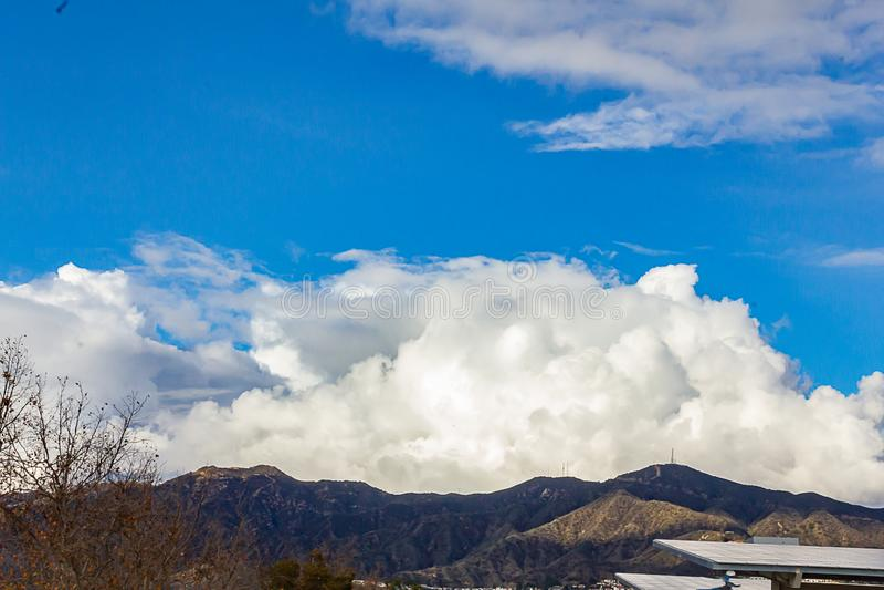 Cumulos, nimbus, облака с горами гребня angeles, голубым небом, солнечным светом, панелями солнечных батарей стоковые фотографии rf