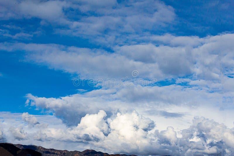Cumulos, nimbus, nuvole con le montagne della cresta di Angeles, cielo blu, luce solare, fotografia stock