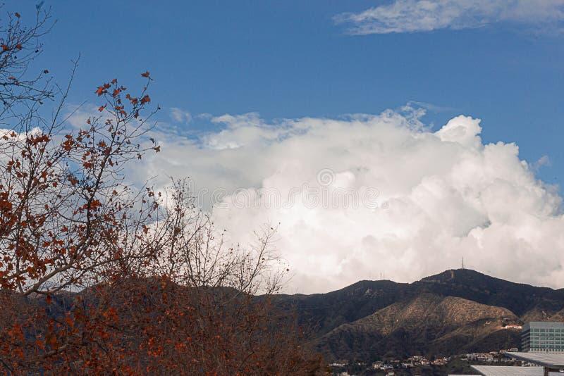 Cumulos, nimbus, nuvole con le montagne della cresta di Angeles, le costruzioni e l'albero del sicomoro fotografie stock