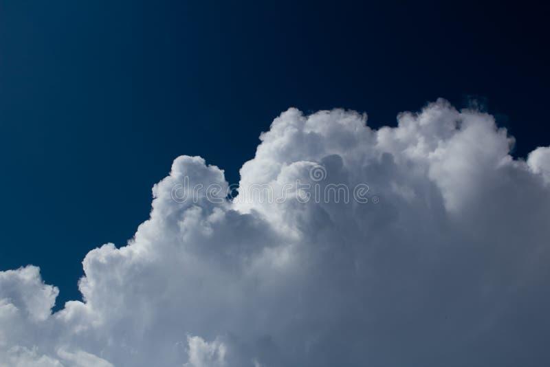 Cumulus blancs sur le fond bleu-foncé de ciel image stock