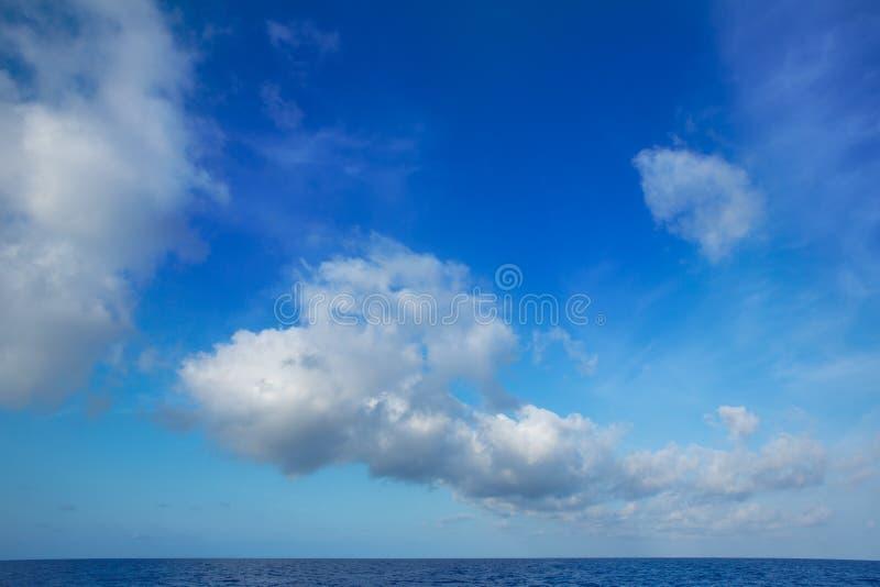 Cumulus chmury w niebieskim niebie nad wodnym horyzontem fotografia stock