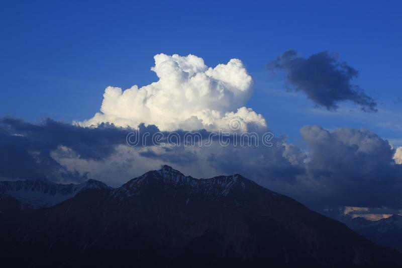 Cumulus cloud over Mount Lenzer Horn, Switzerland. Summer Scene in Canton of Grisons, Switzerland. View from Obermutten stock photo
