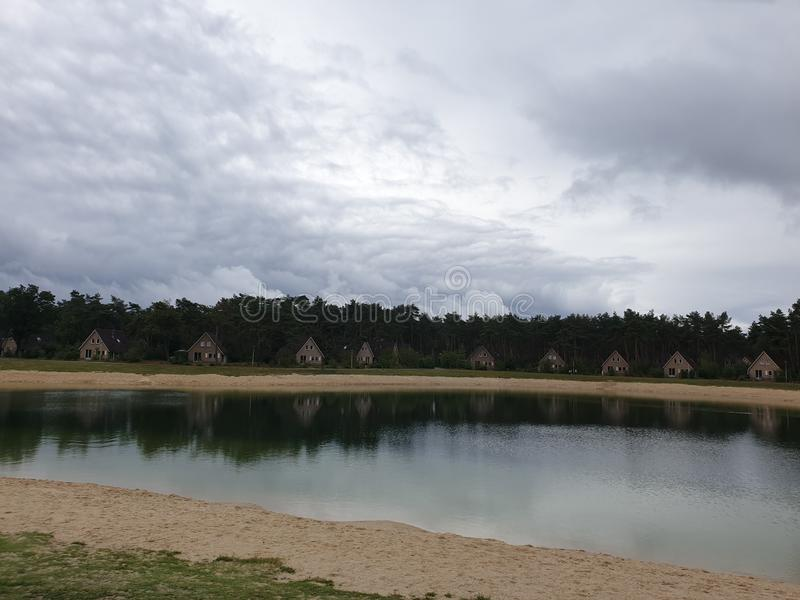 Cumulus clouds above a lake of recreationpark `t Loo in Oldebroek, the Netherlands stock image