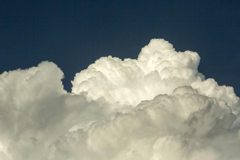 Cumulus clouds at the background of blue sky. Cumulus Clouds. Cumulus clouds are puffy clouds that sometimes look like pieces of floating cotton. The base of stock photo