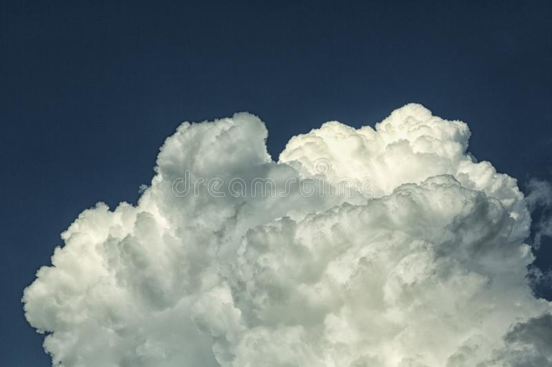Cumulus clouds at the background of blue sky. Cumulus Clouds. Cumulus clouds are puffy clouds that sometimes look like pieces of floating cotton. The base of stock photography