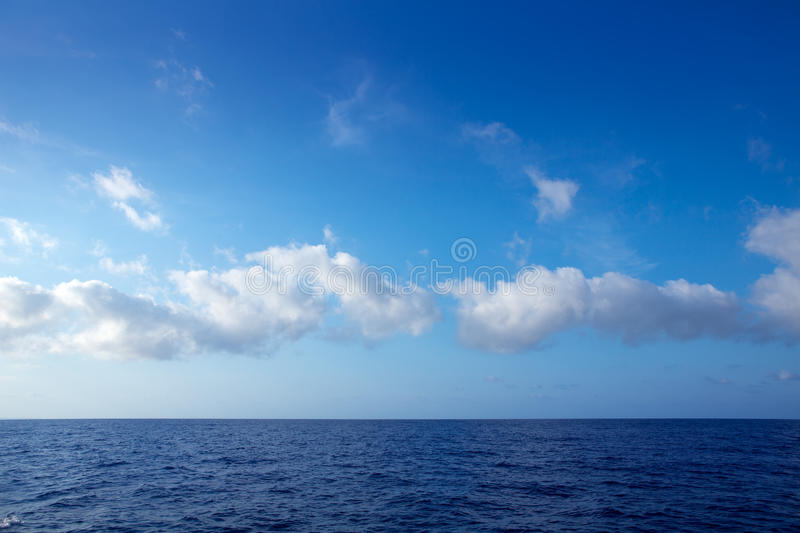 Cumulus clouds in blue sky over water horizon. Cumulus clouds in blue sky over ocean water horizon royalty free stock photography