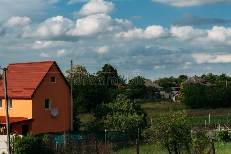 Cumulus clouds over a village in the Black Forest. orange house with a red roof royalty free stock photo