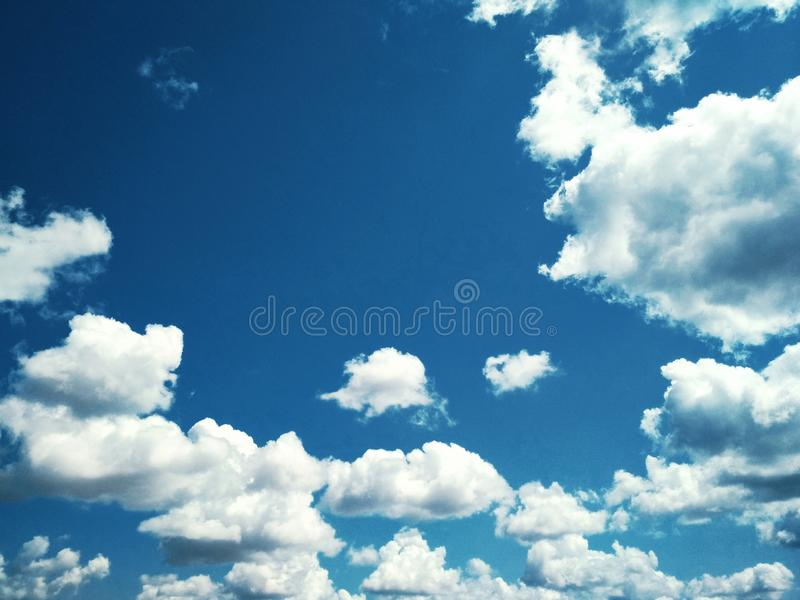 Cumulus clouds peacefully floating in the sky. View of a natural background, wool pack clouds that are peacefully floating in the sky royalty free stock images