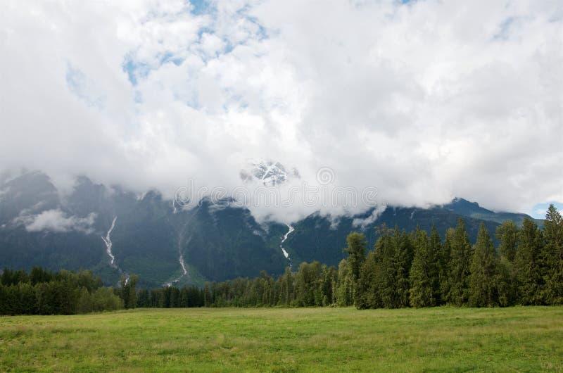Cumulus sur les gammes pittoresques de montagne avec la forêt conifére et les prés verts au pied images libres de droits