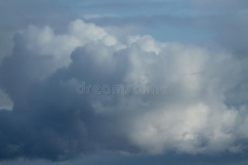 Cumulus white-gray clouds against the blue sky. stock image