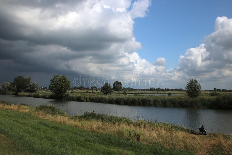 Cumulusnuages sombres au-dessus de la rivière IJssel à Kampen aux Pays-Bas image libre de droits