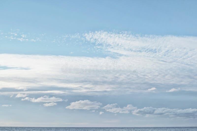 Cumulusu i cirrocumulus chmury w jasnym jaskrawym niebieskim niebie w popołudniu na dennym wybrzeżu z małym paskiem morze pod obrazy stock