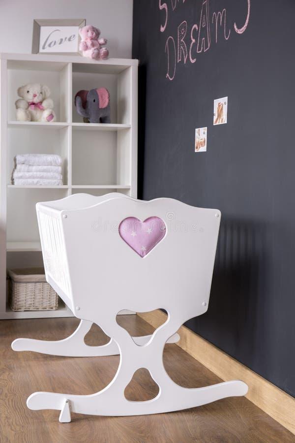Cuna blanca linda en sitio del cuarto de niños imágenes de archivo libres de regalías