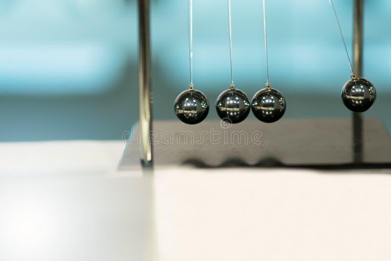Cuna de equilibrio del ` s de Newton de las bolas en fondos borrosos foto de archivo