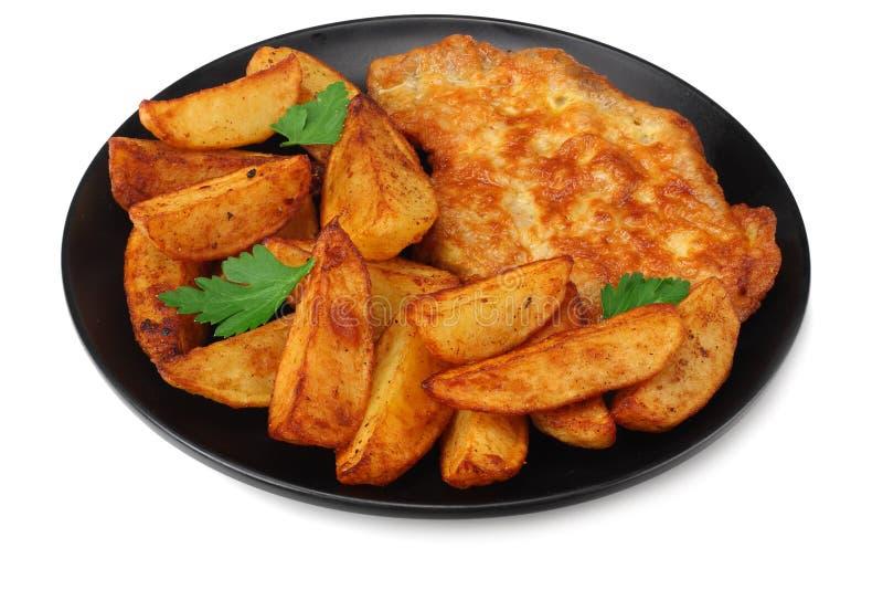 Cunei fritti della patata con la cotoletta sulla banda nera isolata su fondo bianco fotografie stock