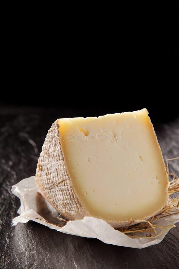 Cuneo di formaggio a pasta semimorbida sul contatore strutturato fotografia stock
