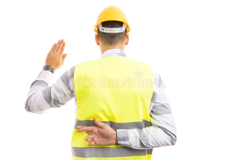 Cunning builder making fake oath or vow hesture. With fingers crossed behind back isolated on white background royalty free stock images