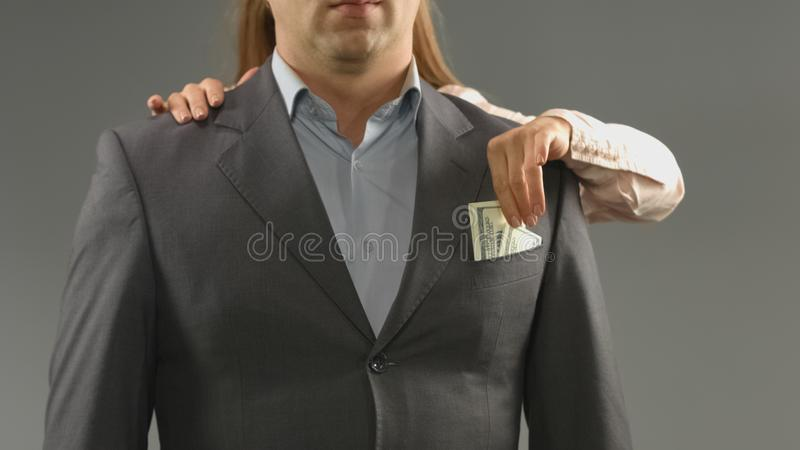 Cunning girlfriend taking cash money from mans pocket, marriage contract, fraud stock photo