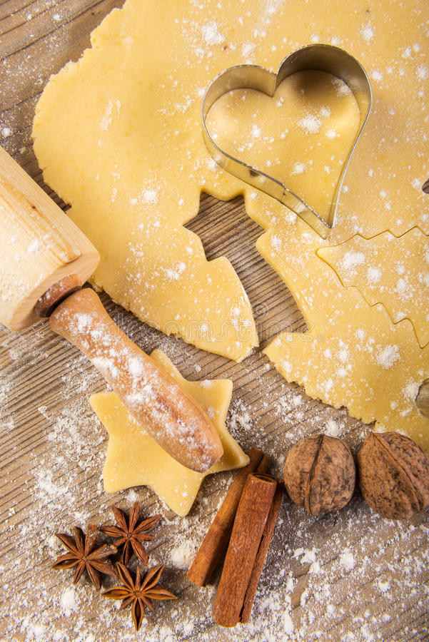 Cuocere, biscotti, matterello e spezie di Natale su legno immagini stock libere da diritti