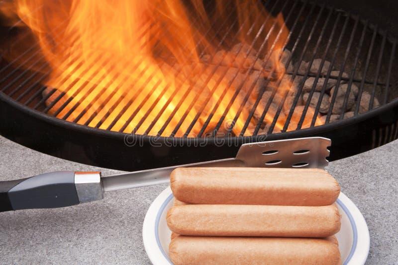 Cuocere i hot dog alla griglia immagine stock libera da diritti