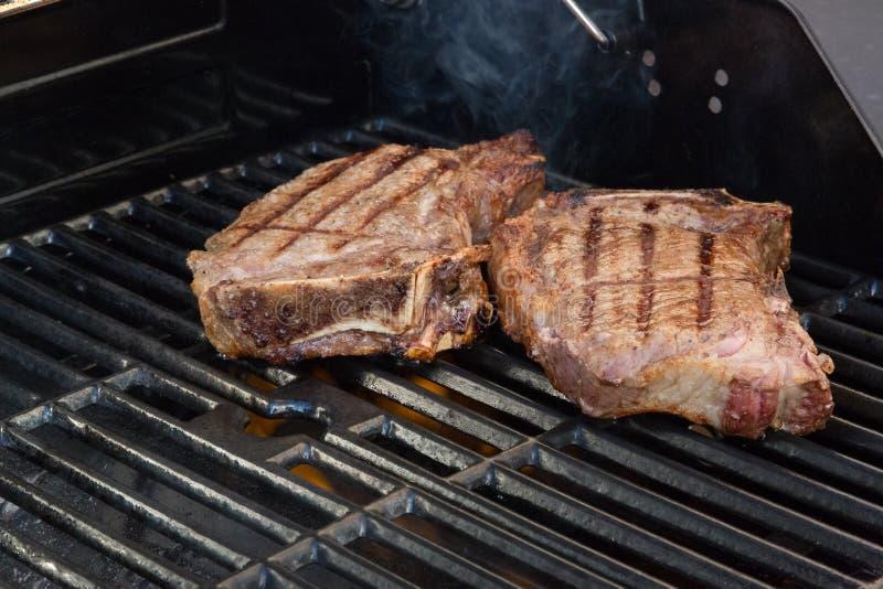 Cuocere le bistecche alla griglia immagini stock libere da diritti