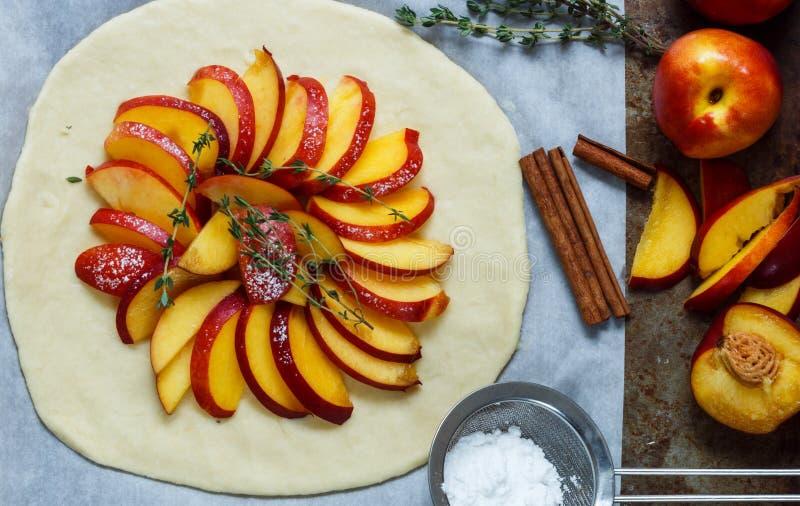 Cuocere una torta della frutta con le pesche, nettarine Gli ingredienti sulla tavola - pasta, pesche, nettarine, zucchero, cannel fotografia stock libera da diritti