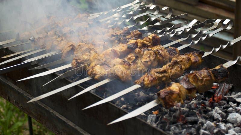 Cuochi della carne sui carboni caldi nel fumo Picnic in natura immagini stock libere da diritti