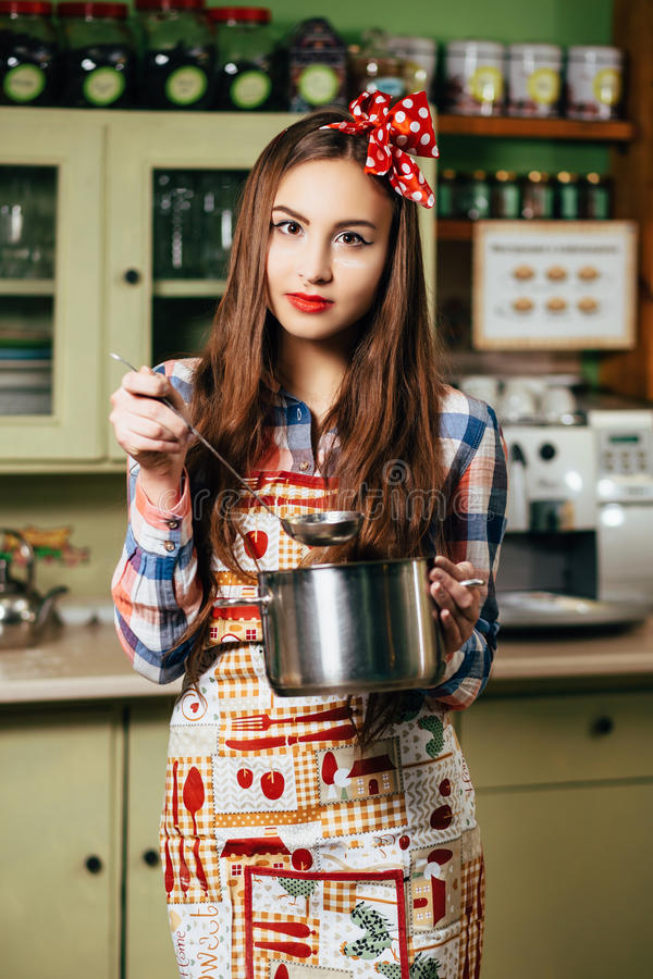 Cuochi della giovane donna nella cucina immagine stock