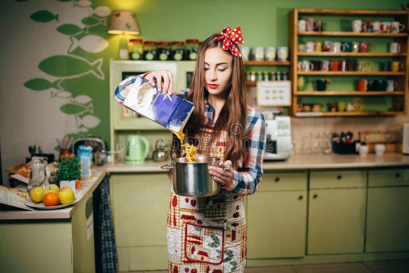 Cuochi della giovane donna nella cucina fotografia stock