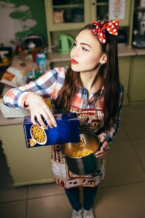 Cuochi della giovane donna nella cucina immagini stock