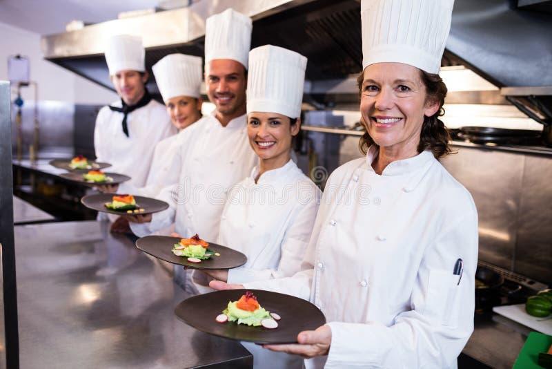 Cuochi unici felici che presentano i loro piatti dell'alimento immagine stock