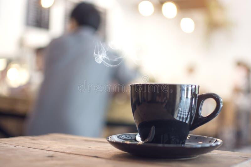 Cuocia a vapore il caffè caldo sulla tavola di legno con l'uomo vago che si siede nel caffè fotografia stock libera da diritti