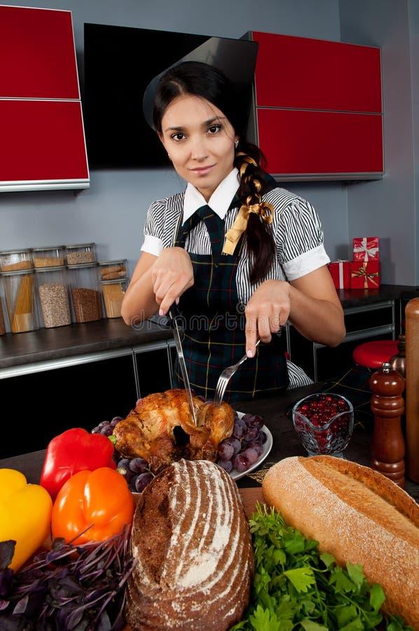Cuoco che della ragazza un tacchino affetta immagine stock