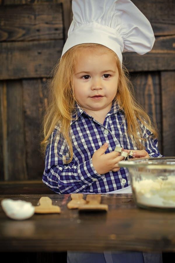 Cuoco del bambino in cappello del cuoco unico con la taglierina del biscotto fotografie stock