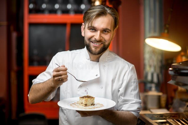 Cuoco del cuoco unico che decora torta di formaggio con cioccolato in polvere fotografia stock