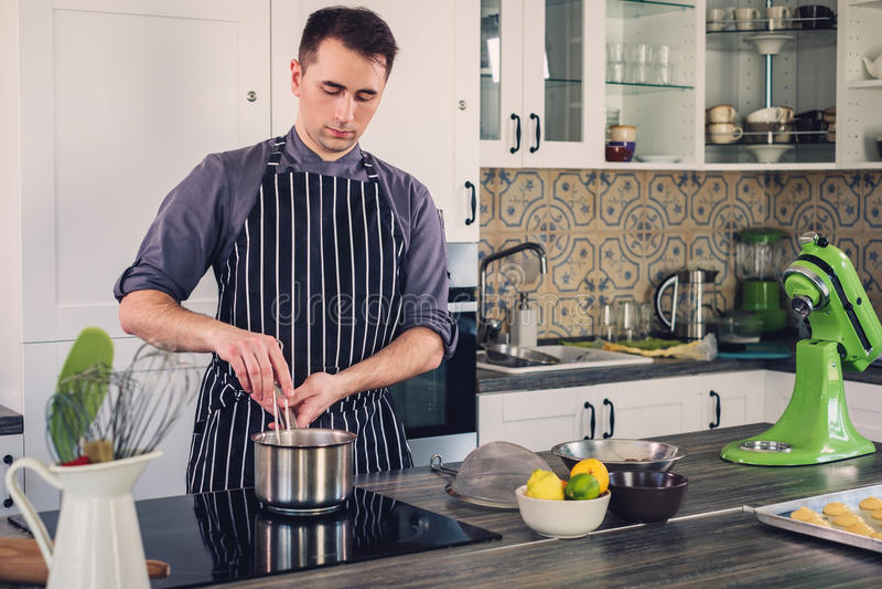 Cuoco del cuoco unico che lavora ad una cucina moderna a casa fotografie stock