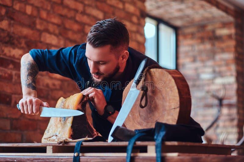 Cuoco del cuoco unico che taglia carne a scatti esclusiva sulla tavola in una cucina con l'interno del sottotetto immagine stock