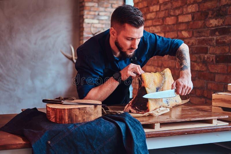 Cuoco del cuoco unico che taglia carne a scatti esclusiva sulla tavola in una cucina con l'interno del sottotetto fotografie stock libere da diritti