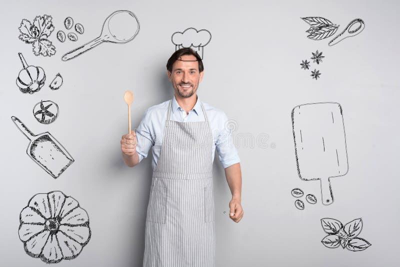 Cuoco emozionale che sorride mentre tenendo un cucchiaio di legno fotografia stock