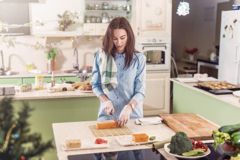 Cuoco femminile che lavora nei guanti che fanno i rotoli di sushi giapponesi che li affettano sulla stuoia di bambù che sta nella immagini stock