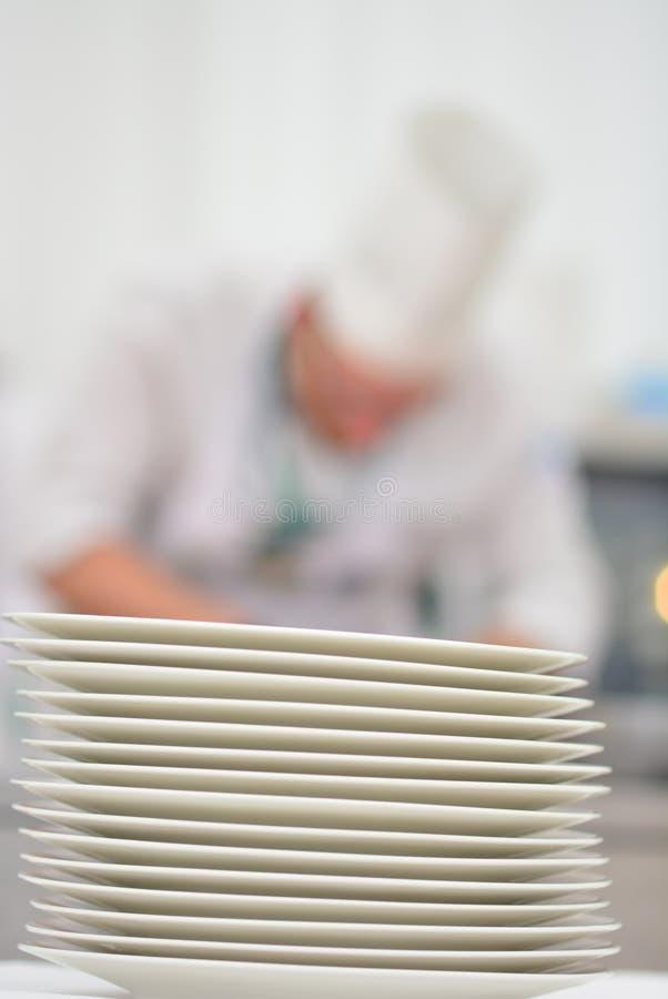 Cuoco in gastronomie Un mucchio dei piatti fotografia stock