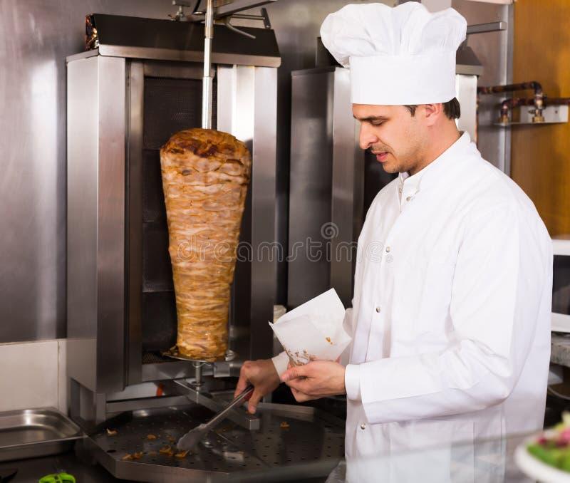 Cuoco indiano che offre kebab saporito al contatore immagini stock