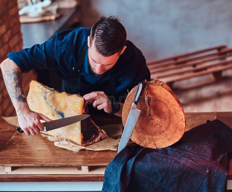 Cuoco messo a fuoco del cuoco unico che taglia carne a scatti esclusiva su una tavola in cucina con l'interno del sottotetto fotografia stock libera da diritti