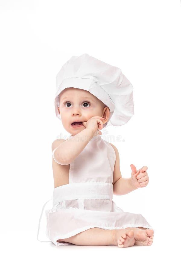 Cuoco unico adorabile divertente del neonato che si siede e che gioca con l'attrezzatura della cucina su un fondo bianco Piccolo  immagini stock