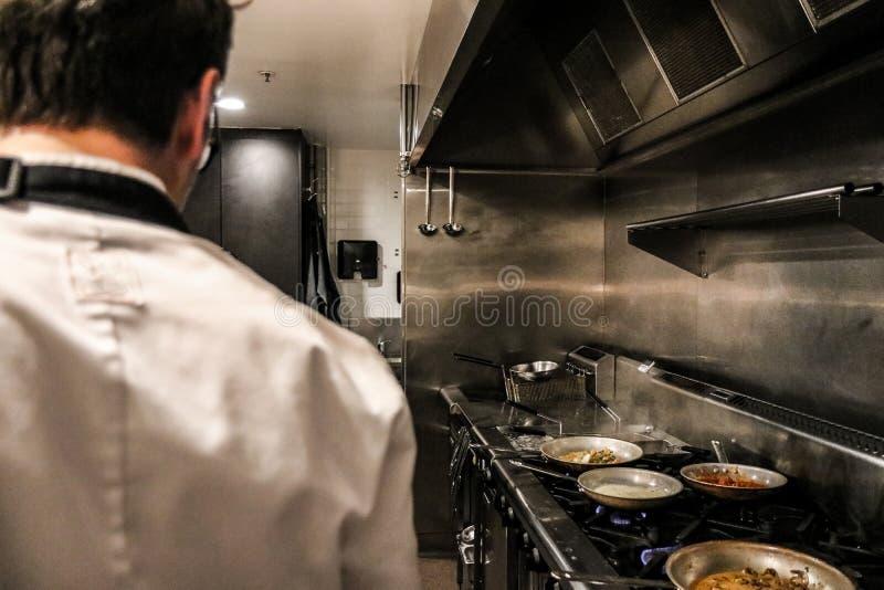 Cuoco unico anonimo che sta sulla cucina del ristorante fotografie stock
