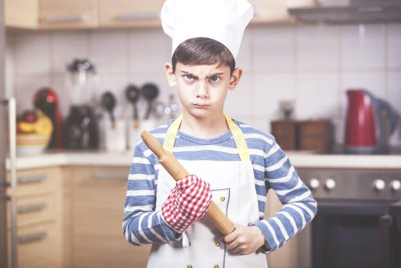 Cuoco unico arrabbiato del ragazzo nella cucina immagini stock
