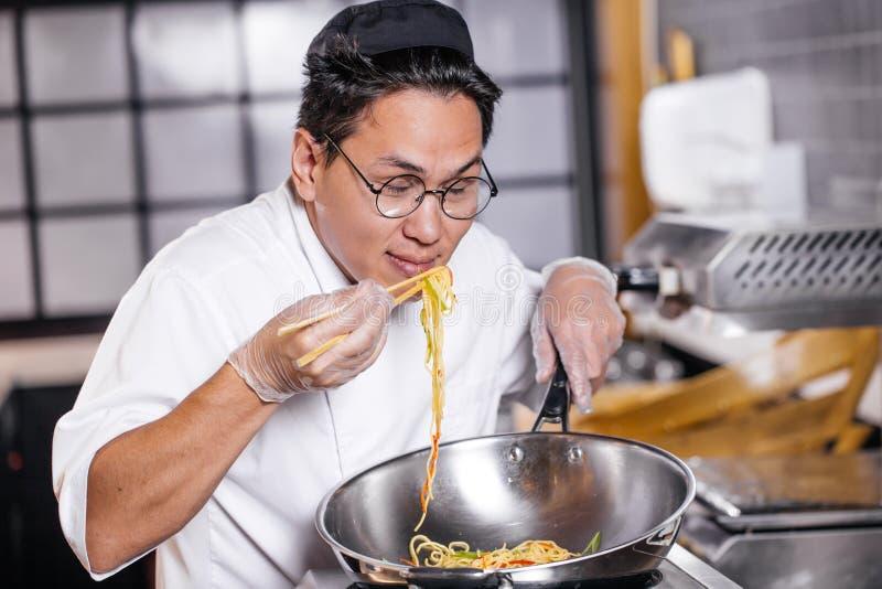 Cuoco unico asiatico attraente che gode mangiando tagliatella fotografie stock