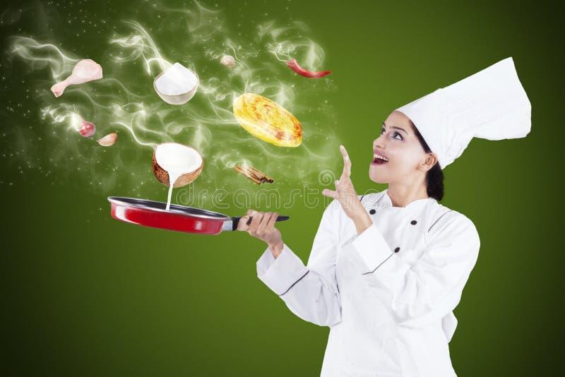 Cuoco unico attraente che cucina con la magia immagini stock libere da diritti