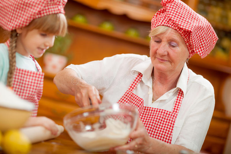 Cuoco unico Baking In Kitchen della nipote e della nonna fotografia stock