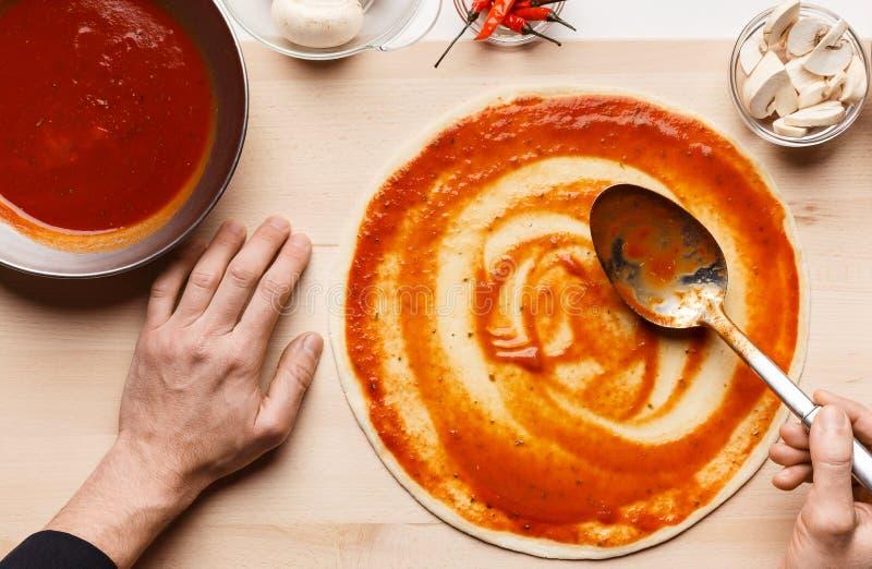 Cuoco unico che cucina pizza, salsa al pomodoro di diffusione sulla base della pizza fotografia stock libera da diritti